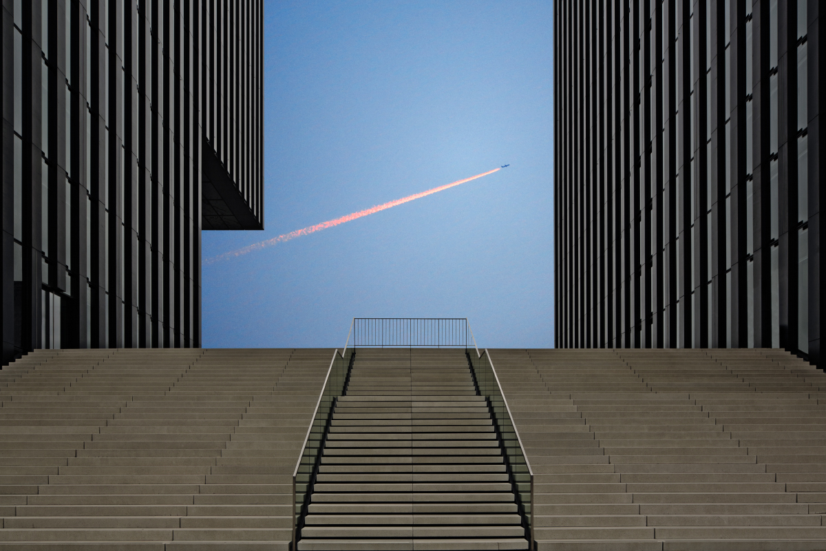 Blick zwischen die beiden Gebaeude des Hyatt Hotel Duesseldorf auf die Treppen. Im Hintergrund Flugzeug am blauen Himmel mit Schweif im Gegenlicht.